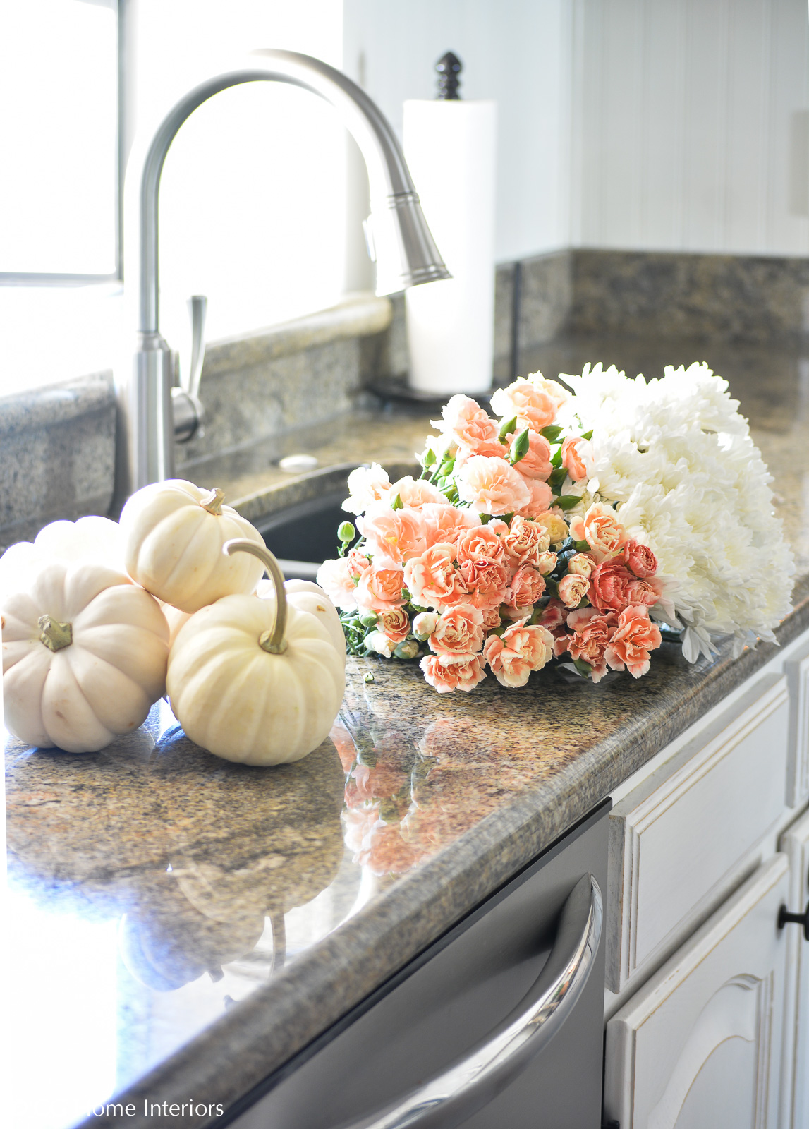 Fall flowers and pumpkins in white kitchen